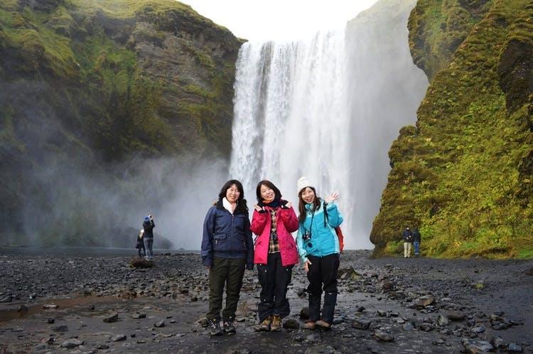 Mach an der Südküste ein Foto von dir vor dem Wasserfall Skogafoss.