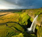 The waterfall Seljalandsfoss cascades over the South Coast cliffs, separating the lowland from the Icelandic Highlands.
