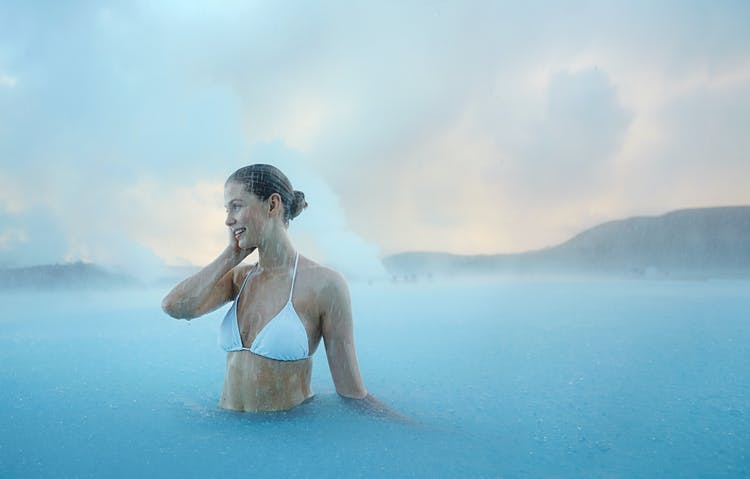 Unwind in the warm, azure waters of the Blue Lagoon before your flight home.