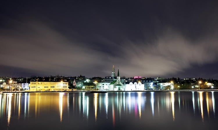 The central city of Reykjavík, reflected in the water of Tjörnin Pond by the City Hall.
