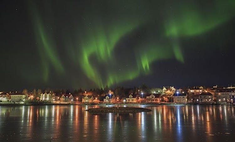 The cityscape of Reykjavík beneath the aurora borealis.