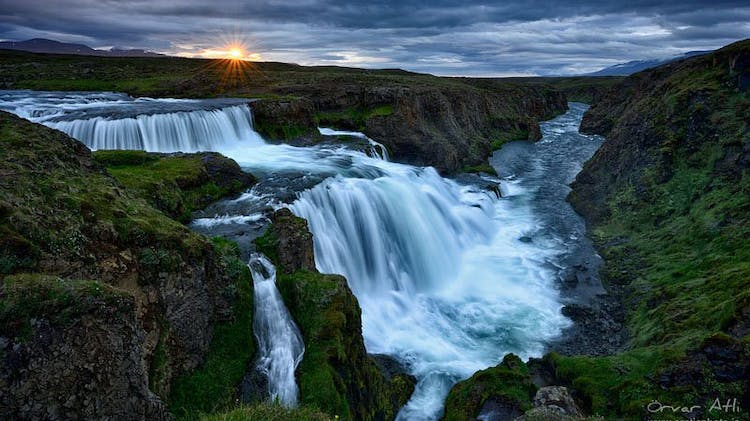 A north Iceland waterfall beneath the setting sun, in the golden hour that goes all the way through Iceland's summer nights.