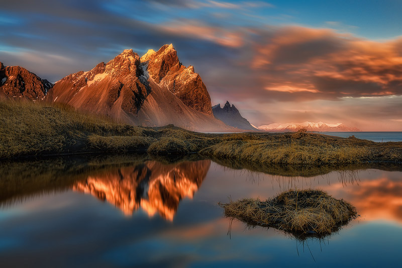The rugged peaks of Vestrahorn Mountain in East Iceland, bathed by the rays of the midnight sun.