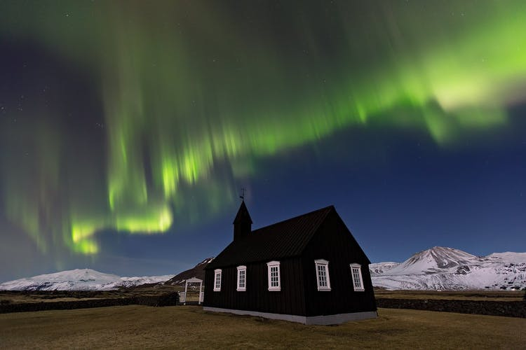 The black church at Búðir bathed in the glow of the Northern Lights, on the Snæfellsnes Peninsula in West Iceland.