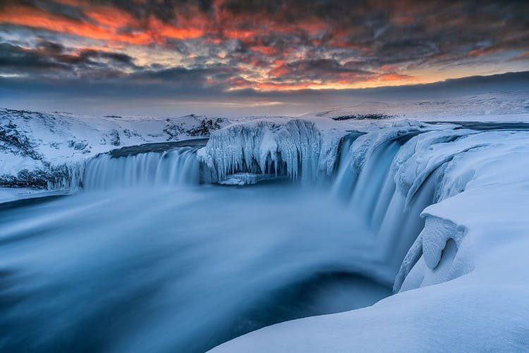 Goðafoss Waterfall in North Iceland drenched in snow and ice under the late winter sunrise.