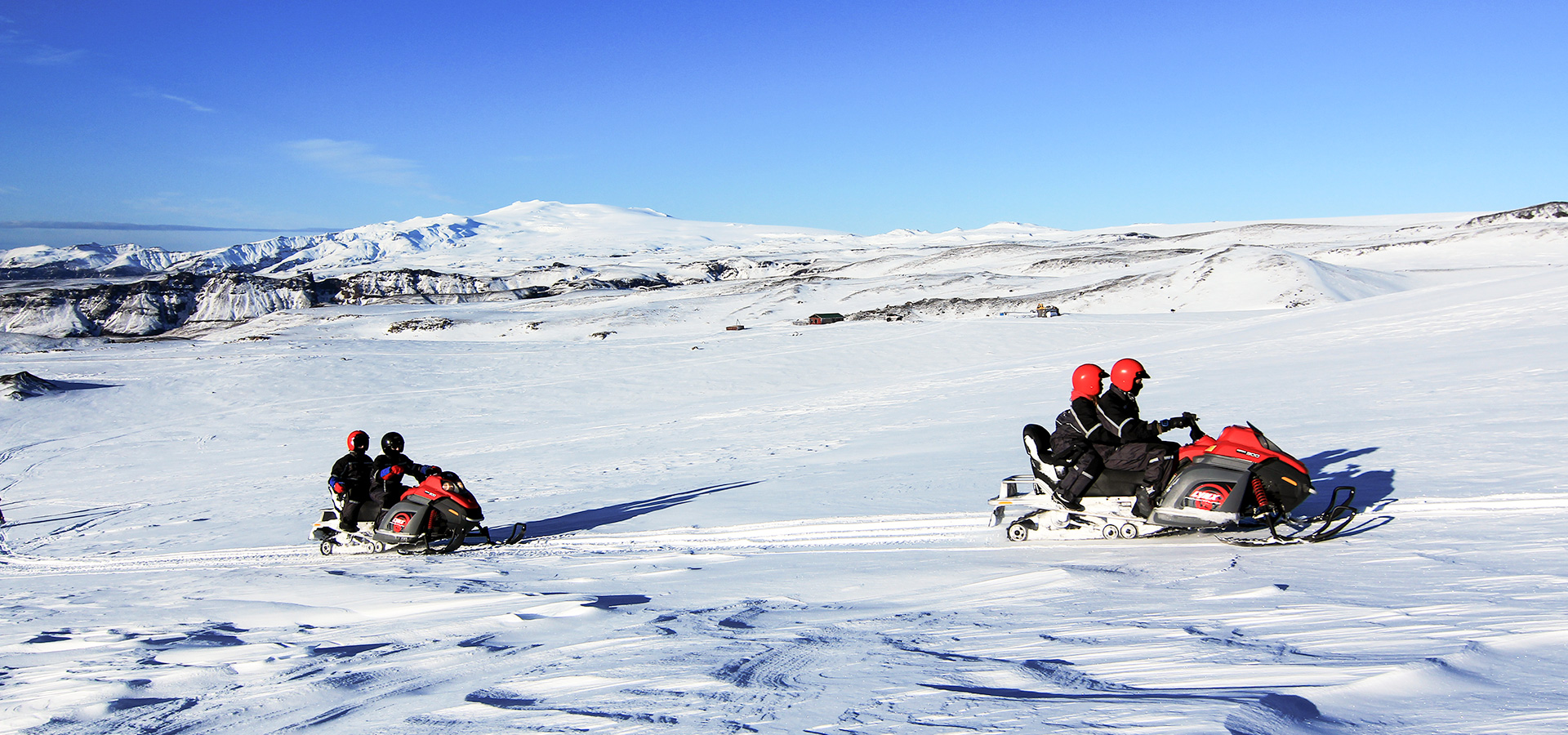 Snowmobiling tours require two riders per vehicle while zipping across Mýrdalsjökull Glacier.