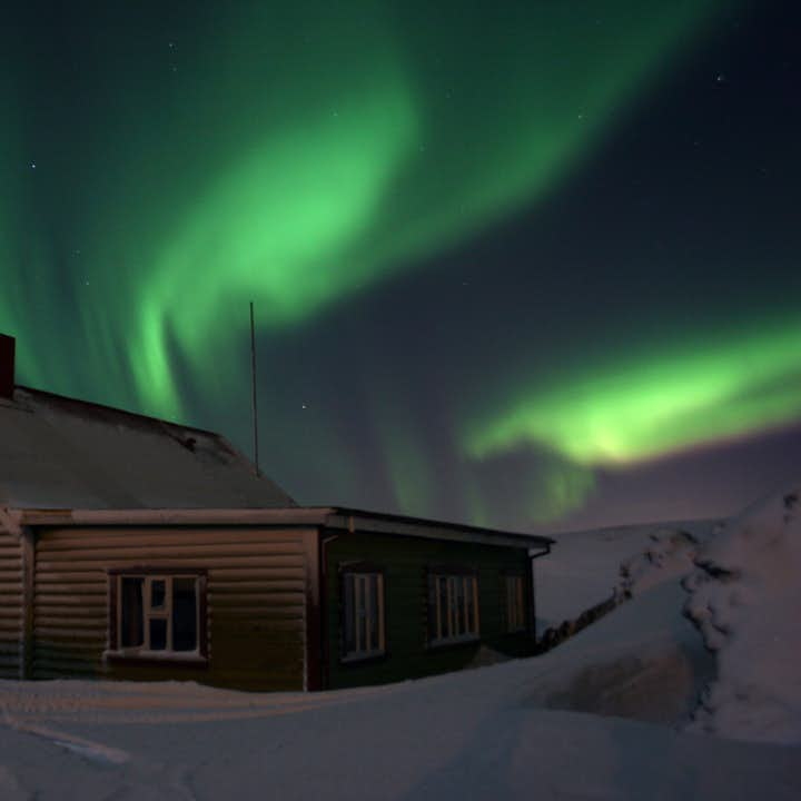 The aurora borealis dancing over a countryside cottage.
