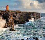 A lighthouse on the Snæfelssnes Peninsula that overlooks tall cliffs.