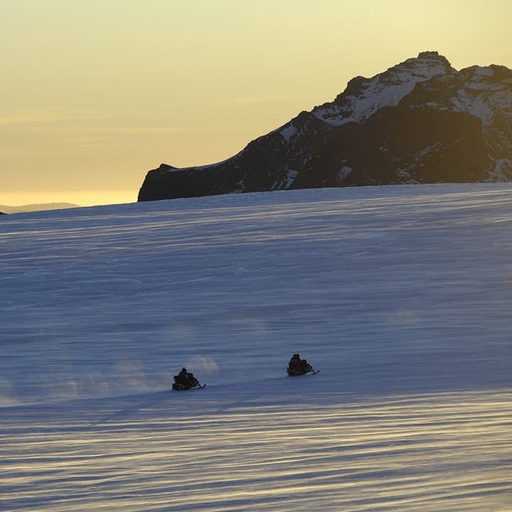 Enjoy the snowy views of Langjökull glacier by zooming through them on a snowmobile.