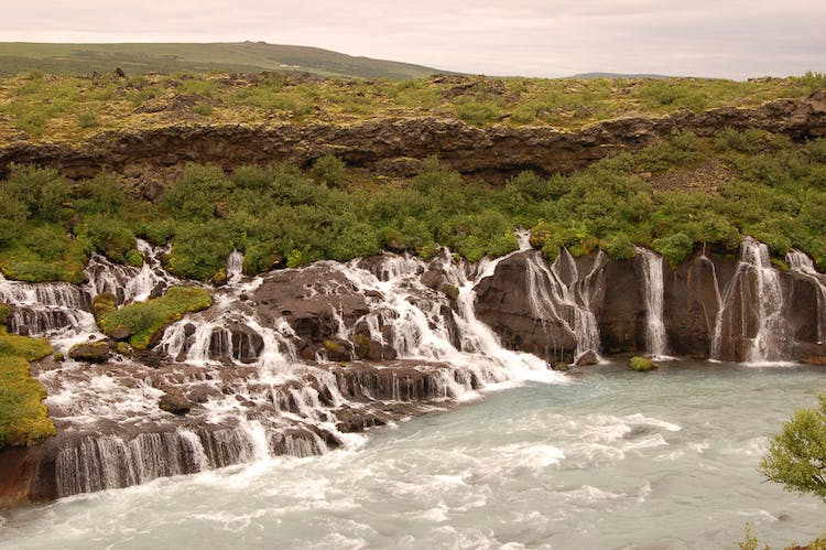 Hraunfossar is best described as a series of waterfalls pouring out from a porous lava field.
