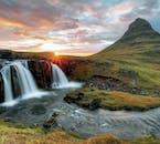 The midnight sun peaks from the horizon, behind Kirkjufell and Kirkjufellsfoss.