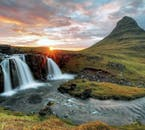 The midnight sun peaks from the horizon, behind Kirkjufell and Kirkjufellsfoss.