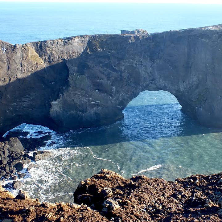 The massive rock arch at Dyrhólaey peninsula on the South Coast bathed in the summer sun's rays.
