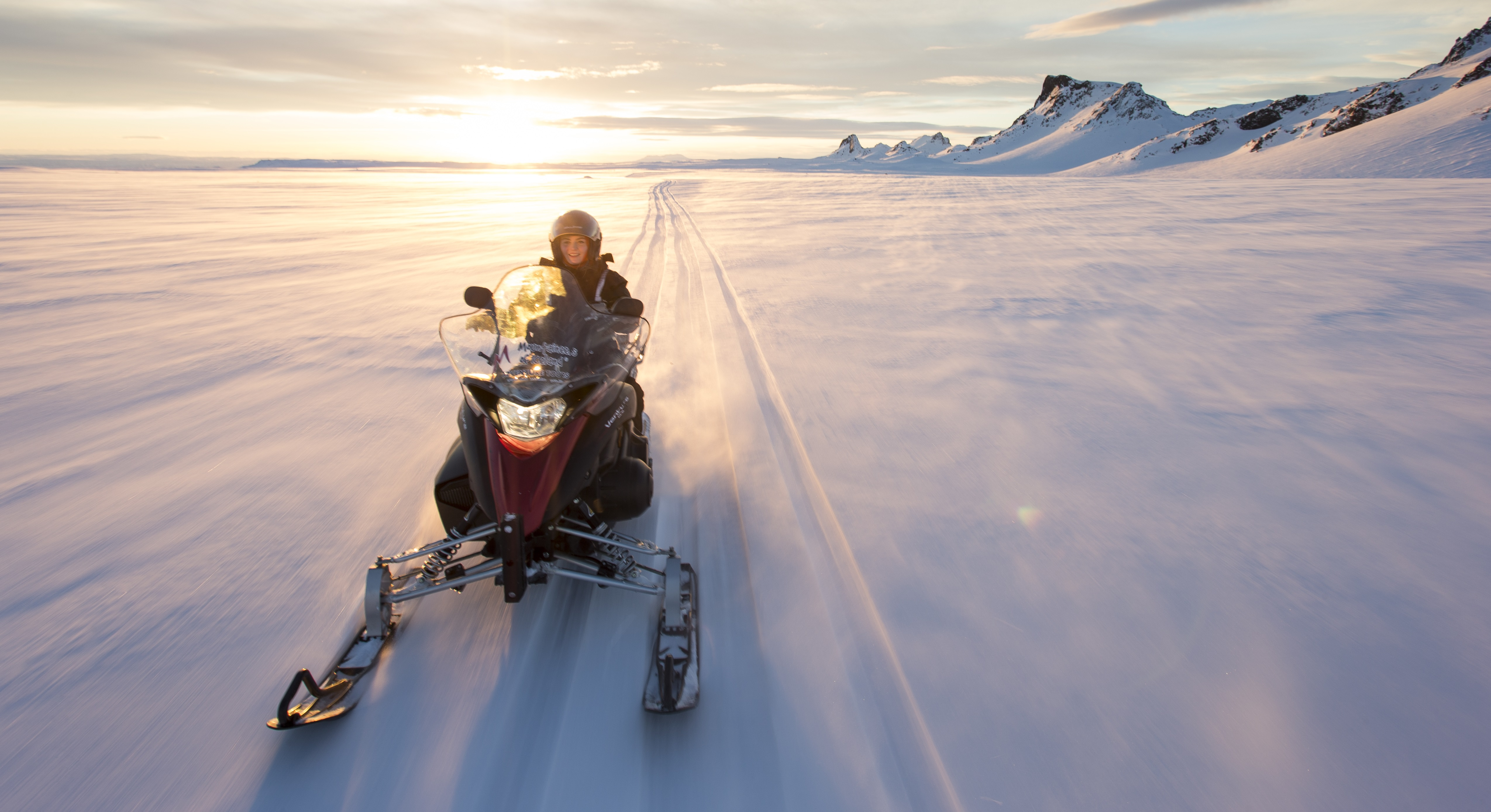 在朗格冰川之巅体验刺激的雪地摩托。