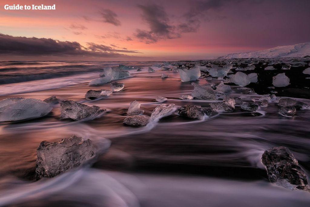 Bølger og isbjerge på Diamantstranden ved solnedgang.