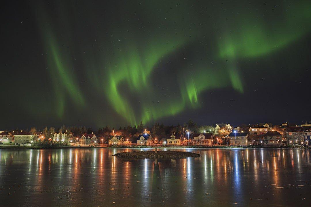 Aurora boreal sobre el estanque de la ciudad en Reikiavik