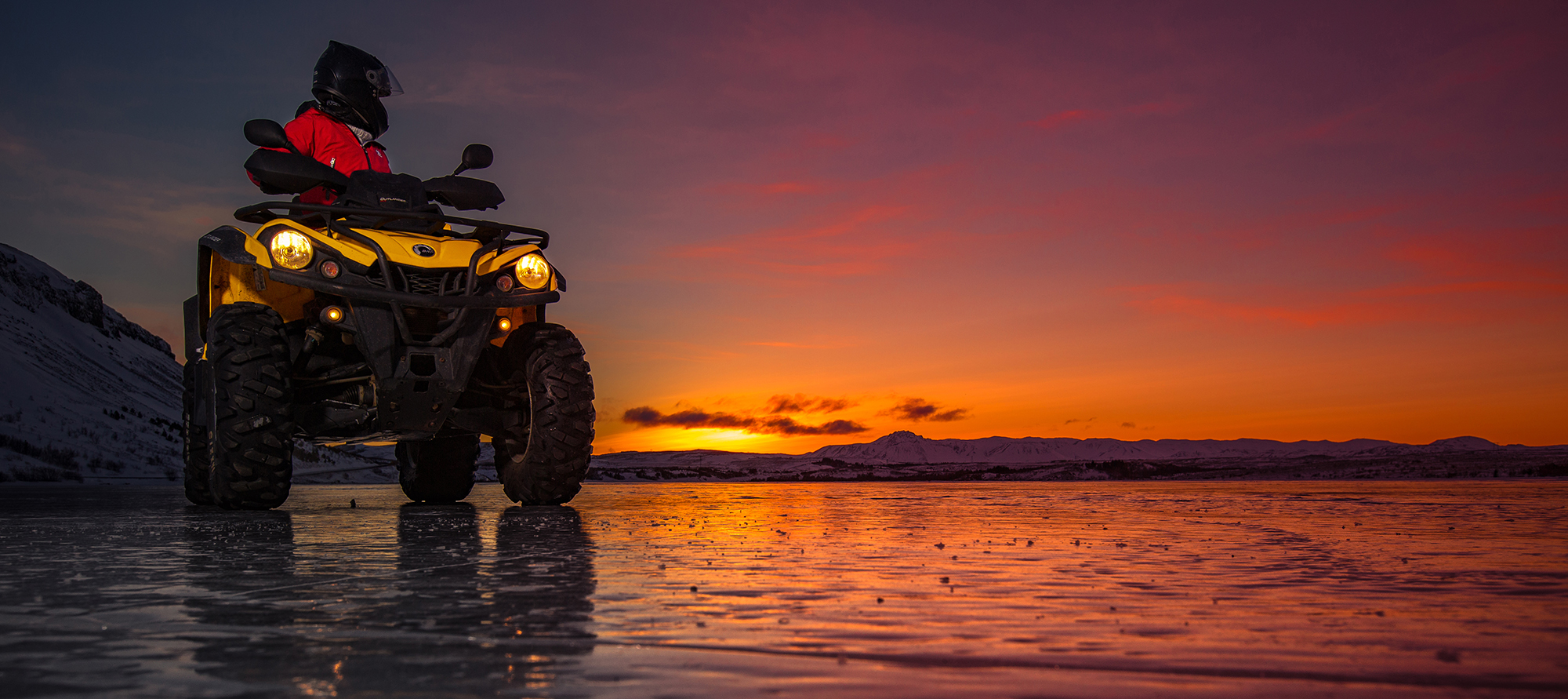 A quad standing on the shores of Hafravatn in the midnight sun.