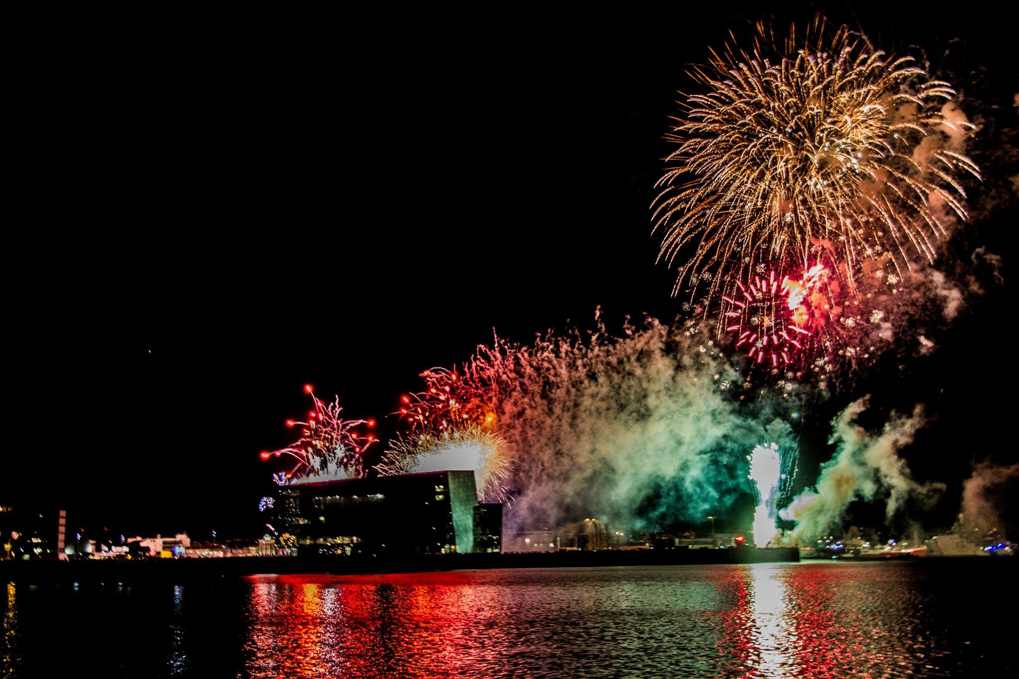 Fireworks during New Year's in Iceland casting their lights on Harpa Concert Hall.