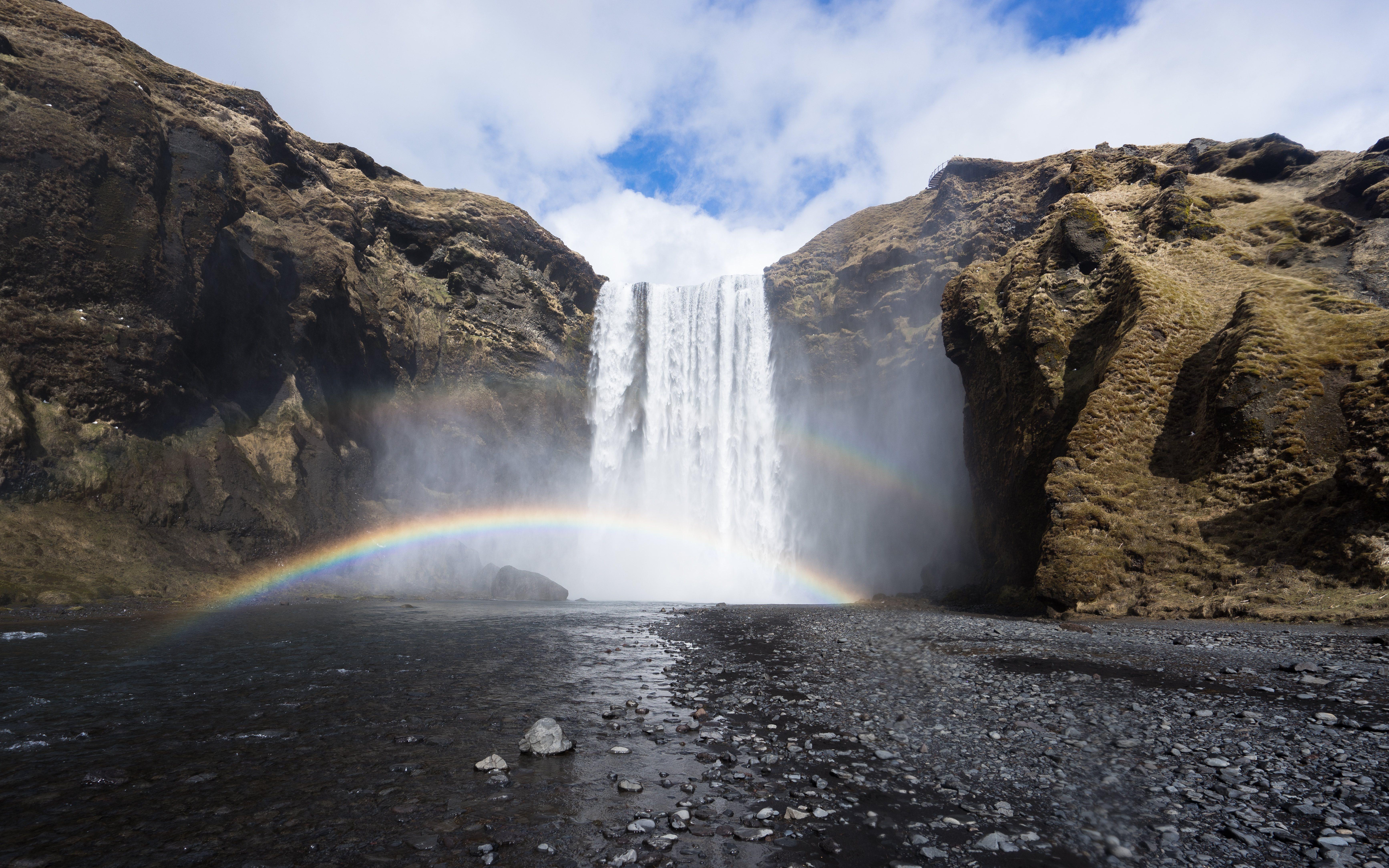 Un arco iris formado por el sol y el rocío de la poderosa cascada Skógafoss.