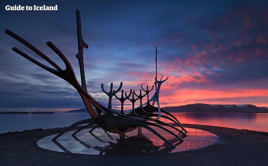 Sólfarið (Ship of the Sun) by Reykjavík's coastline. Mount Esja is bathed in red across the bay.