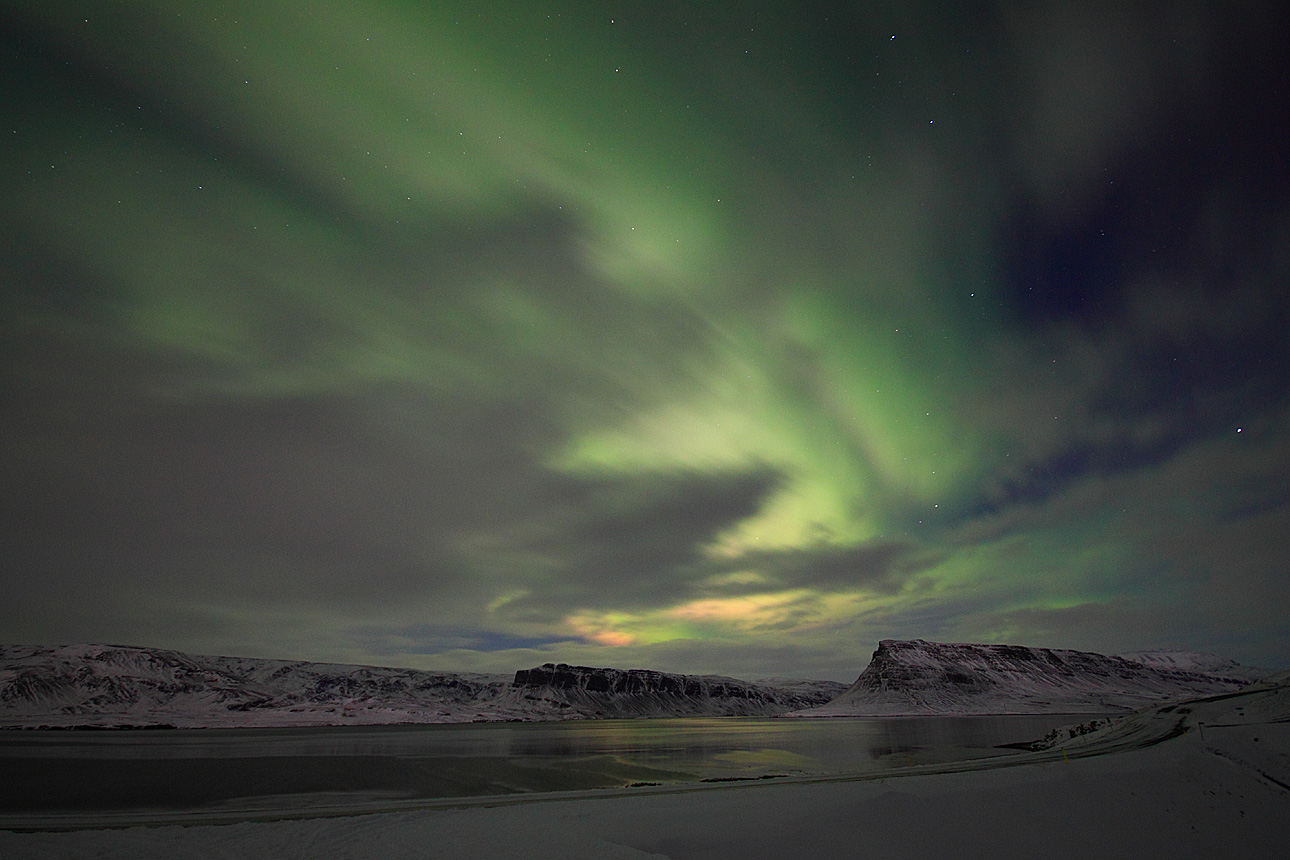 The Northern Lights mixing with a veil of soft clouds.
