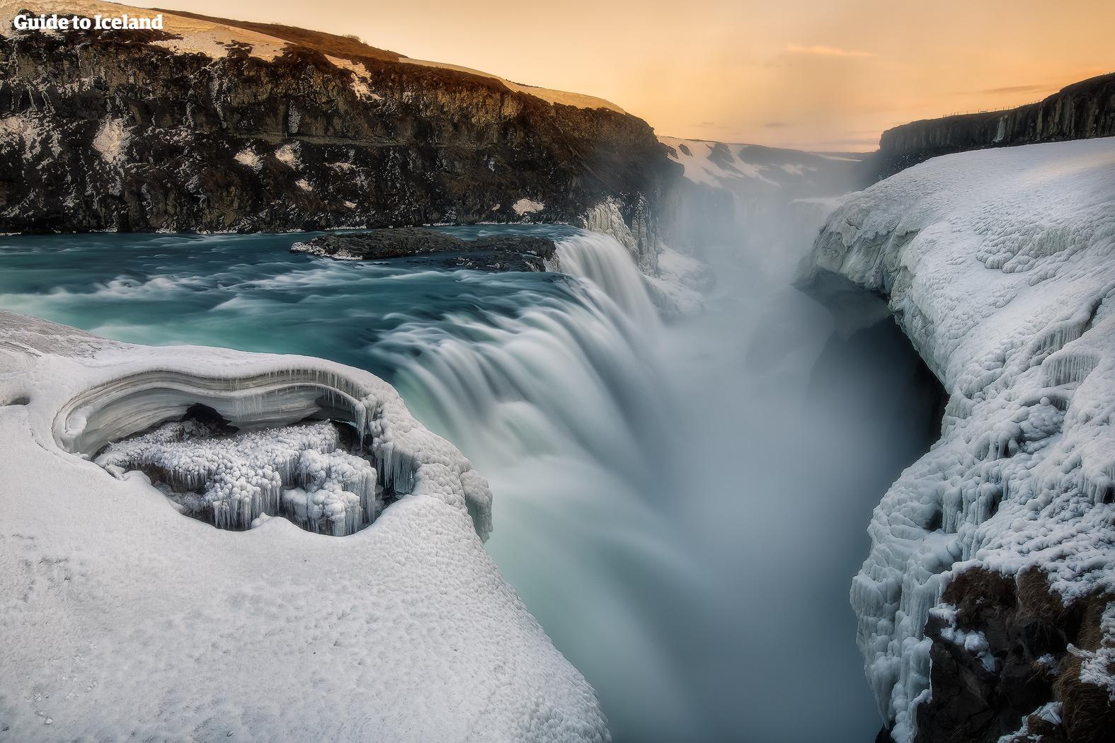 Gullfoss stürzt donnernd in eine uralte Schlucht, die im Winter von dicken Schichten aus Eis und Schnee bedeckt ist.