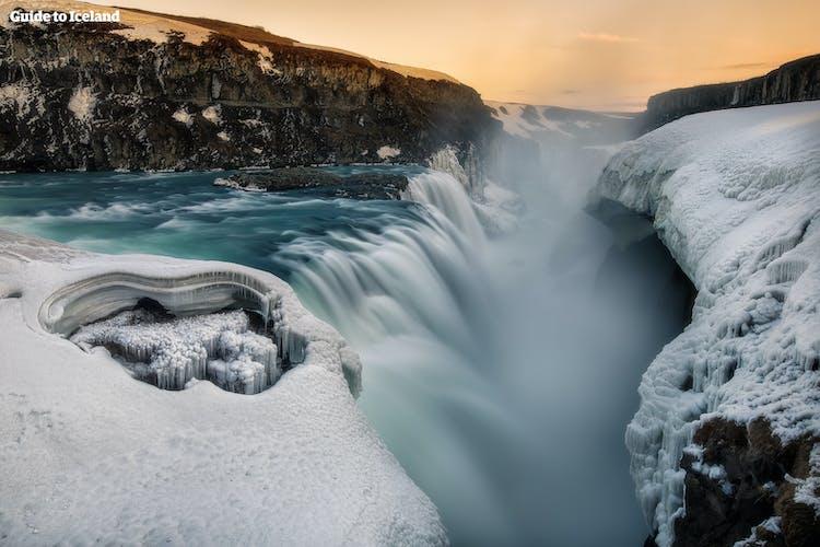 Водопад Гюдльфосс с грохотом обрушивает речные воды на дно древнего каньона, которое в зимнее время года спрятано под толстым слоем снега и льда.
