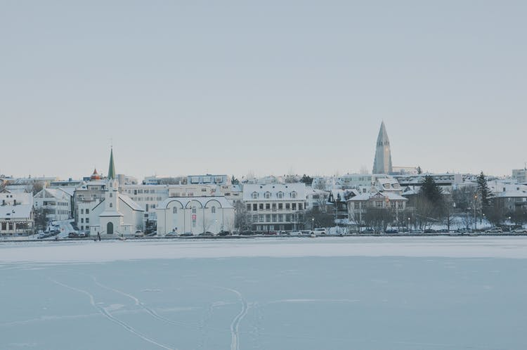 Across the solidly frozen lake of Tjörnin, visitors can admire the snowy skyline of Reykjavík city.