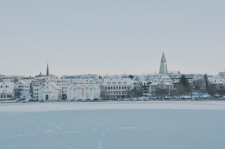 Po zamarzniętym jeziorze Tjörnin można podziwiać śnieżną panoramę miasta Reykjavík.