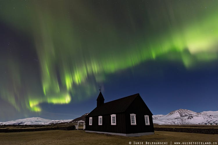 Above the black church of Buðir in west Iceland, the Northern Lights snake across the night sky in winter.