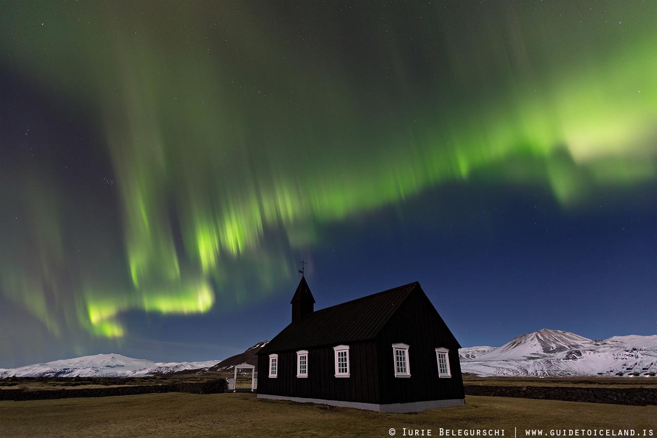 Nad czarnym kościołem Buðir w zachodniej Islandii zorza polarna wije się zimą po nocnym niebie.