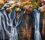 Goteando a través de la lava cubierta de vegetación helada se encuentran los numerosos riachuelos de la cascada Hraunfossar en el oeste de Islandia.