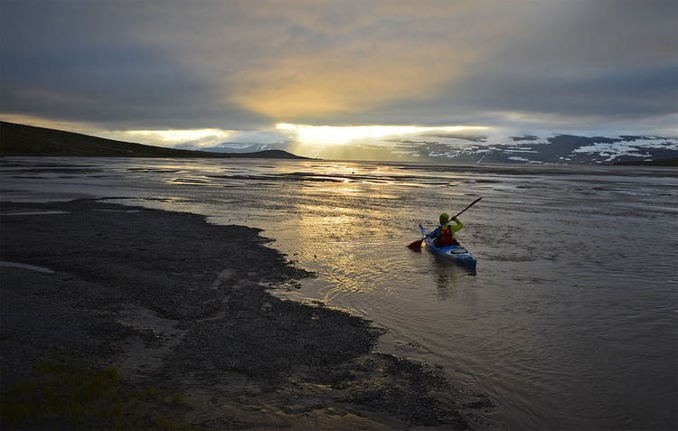 Kayaking under the midnight sun in the Hornstrandir region of the Westfjords.