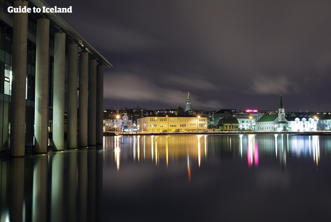 Die Lichter von Reykjavik spiegeln sich in der ruhigen Wasseroberfläche.