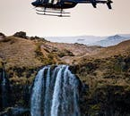 A helicopter flies over the west Iceland waterfall Glýmur.