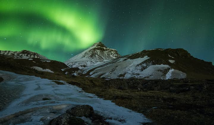 The Northern Lights dancing above the snowy, icy mountains of Iceland's west.