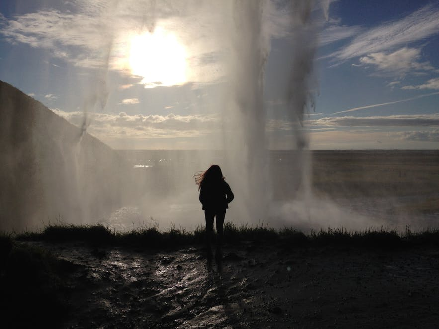 Standing behind Seljalandsfoss waterfall in Iceland