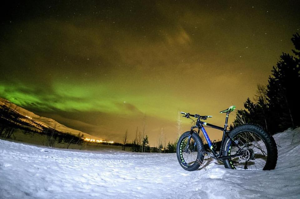 一辆专为户外地形设计、格外适合冰岛冬季路况的胖胎自行车,停放在了北极光下