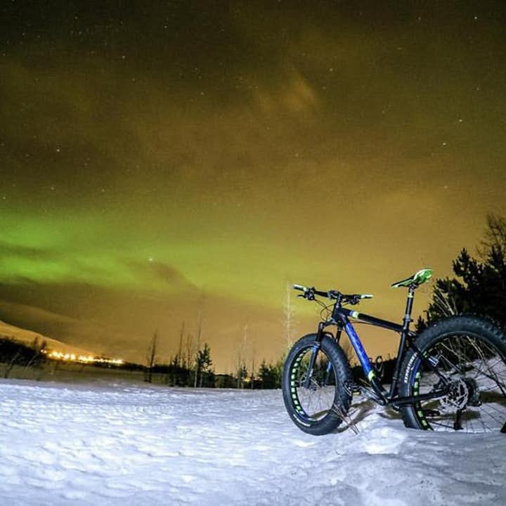 A fat bike capable of trekking through snow, under a dazzling display of the Northern Lights.