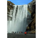 Skógafoss waterfall thunders off a dramatic cliff, and it is possible to walk right up to the falling water.