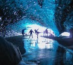 Un groupe appréciant la beauté d'une grotte de glace sious le glacier Vatnajökull, en Islande du Sud, en hiver.