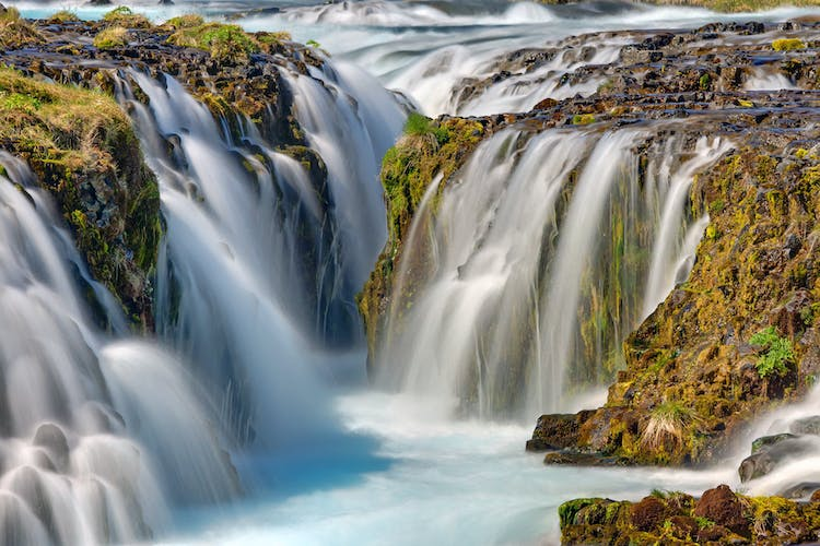 The waterfalls of West Iceland cascade over fields of rugged lava rocks.