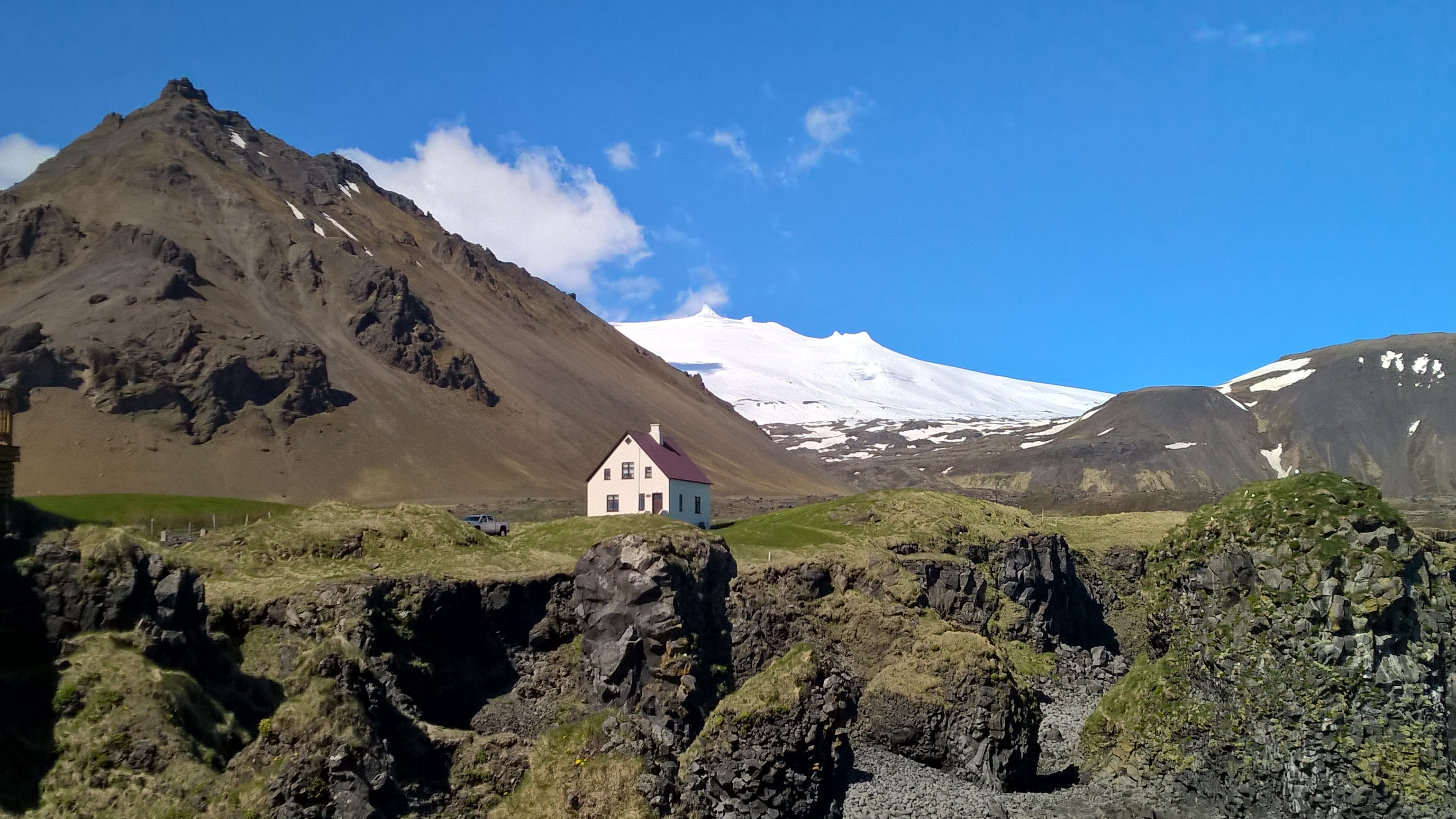The magnificent Snæfellsjökull rises over an old farm and lava field on the tip of West Iceland's Snæfellsnes Peninsula.