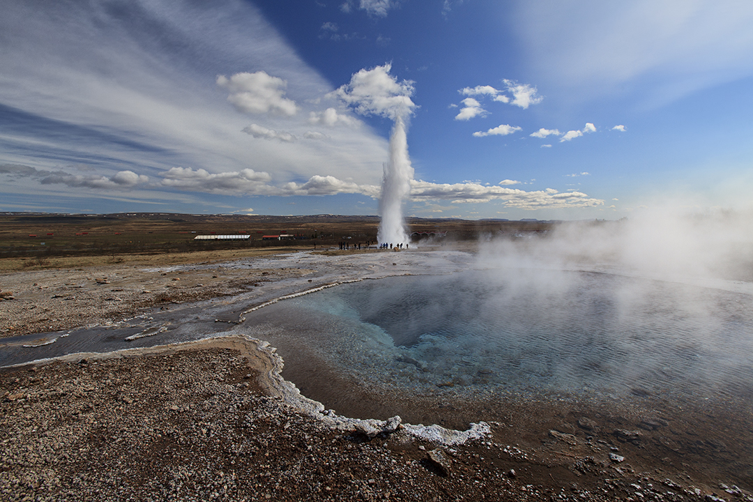 Strokkur in mid-explosion, a stark contrast to the now dormant Geysir hot spring.