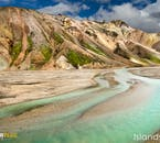 An azure river runs through rhyolite mountains in the highlands of Iceland.