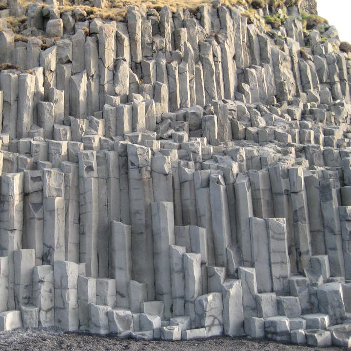 Hexagonal basalt columns can be found on Iceland's South Coast, particularly around the cliffs and arch of Dyrhólaey.