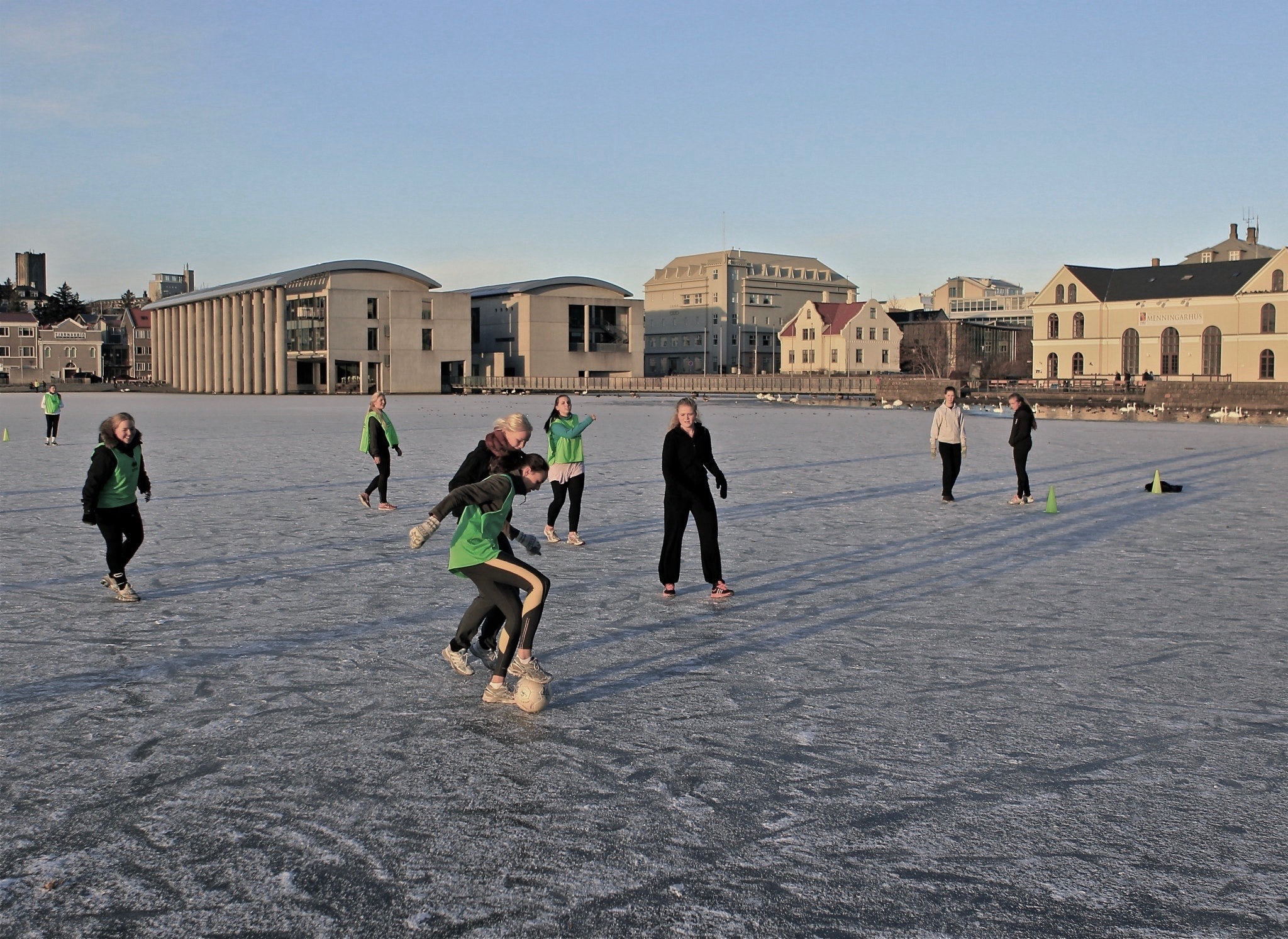 Girls playing football on an icy pond in front of Reykjavík city hall