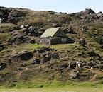 กระท่อมที่เก่าแก่กลางภูเขาบนดอยของประเทศไอซ์แลนด์ ถูกล้อมรอบด้วยก้อนหิน เหมือนบ้านที่ชาวไอซ์แลนด์ใช้กันในสมัยก่อนเมื่อหลายร้อยปีที่แล้ว.