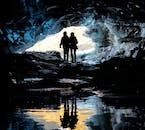 Les silhouettes se reflètent parfaitement dans l'eau immobile dans une grotte de glace bleue.