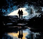 Silhouettes perfectly reflected in still water within a blue ice cave.